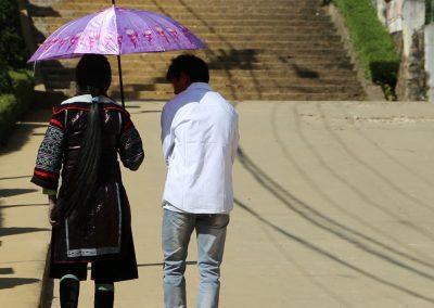 Hmong boy walking along side a girl carrying an umbrella